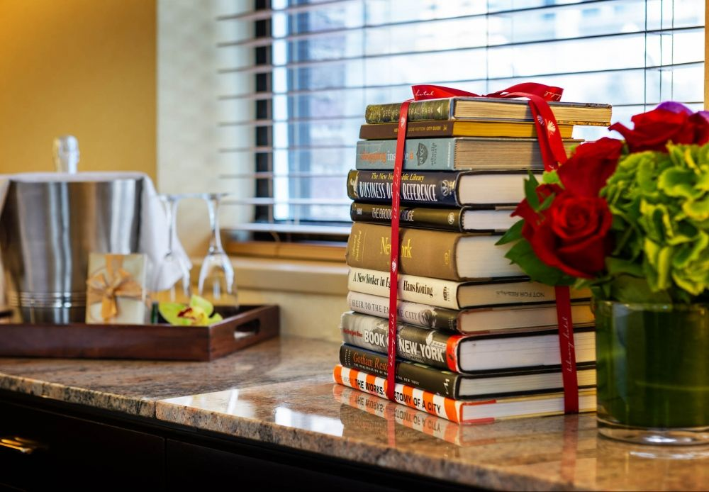 stack of books, floral arrangement, bottle of chilled champagne